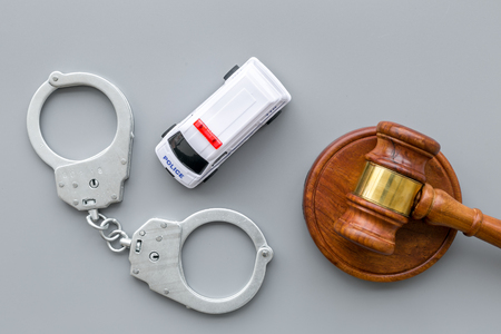 Crime concept. Police car toy, handcuff, judge hammer on grey background top view