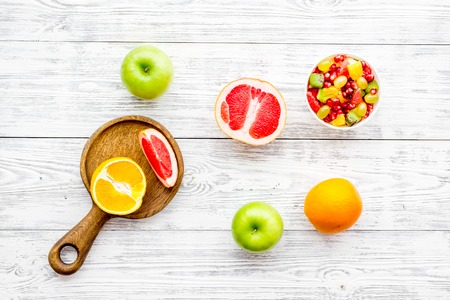 Food rich by vitamins and fiber. Healthy food. Fruit salad near fresh fruits on white wooden background top view Stock Photo