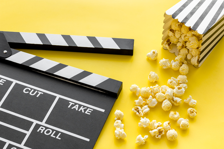 Movie premiere concept. Clapperboard and popcorn on yellow background Banque d'images - 116166027