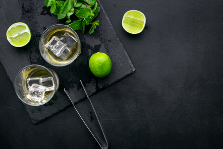 Alcoholic beverage. Whiskey with ice, mint and lime on black background top view copy space