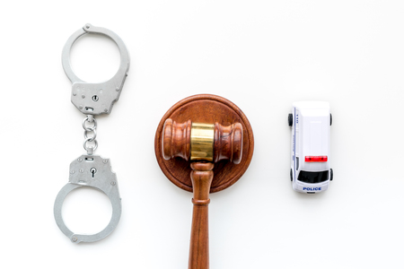 Crime concept. Police car toy, handcuff, judge hammer on white background top view