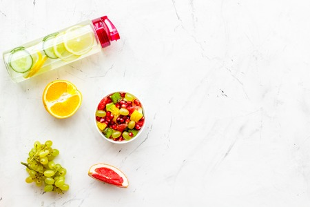 Diet rich in fruits. Slimming diet. Fruit salad near fruit lemon and cucumber water on white stone background top view copy space Stock Photo