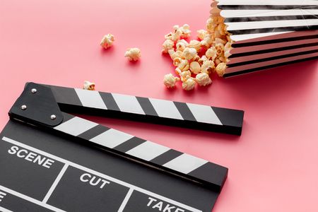 Film watching concept. Clapperboard and popcorn on pink background copy space Banque d'images - 116257414