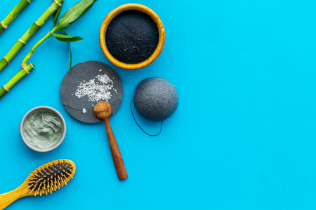 Hair care, hair spa. Cosmetics based on bamboo charcoal powder near comb on blue background top view copy space Stock Photo - 116257457