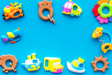 Handmade toys for newborn babies boys, plastic and wooden rattle on blue background top view space for text frame