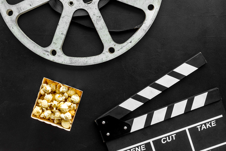 Movie premiere concept. Clapperboard, film stock, popcorn on black background top view Banque d'images - 116257465