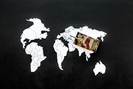 Military action, military threat concept. Tanks toy on world map on black background top view