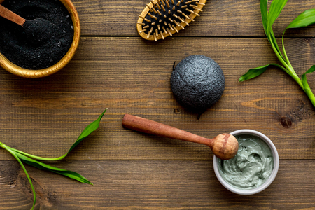 Skin cleansing and detox. Bamboo charcoal powder cosmetics on dark wooden background top view