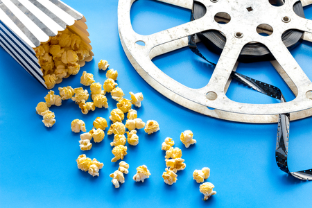 Cinema concept. film stock and popcorn on blue background
