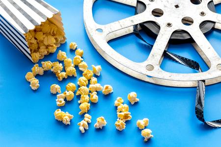 Kinokonzept. Filmvorrat und Popcorn auf blauem Hintergrund Standard-Bild