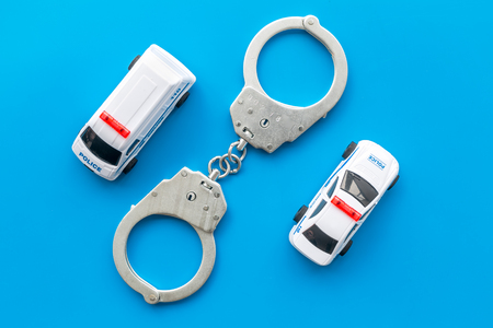 Police concept. Police car toy and handcuff on blue background top view Stock Photo