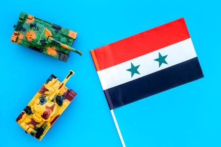 War, military threat, military power concept. Syria. Tanks toy near Syrian flag on blue background top view Stock Photo - 116257498