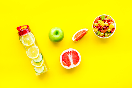Weight loss concept. Fruit salad near fruit lemon and cucumber water on yellow background top view