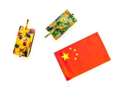 War, military threat, military power concept. China. Tanks toy near Chinese flag on white background top view