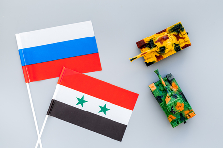 War, confrontation concept. Russia, Syria. Tanks toy near Russian and Syrian flag on grey background top view