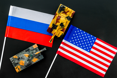 War, confrontation concept. Russia, USA. Tanks toy near Russian and American flag on black background top view