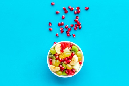 Light healthy breakfast or appetizer. Fruit salad with apple, kiwi and pomegranate in bowl on blue background top view.