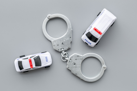 Police concept. Police car toy and handcuff on grey background top view.