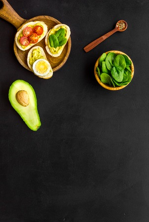 Make avocado bruschettas. Toasts with vegetables and guacamole on black background top view. Foto de archivo - 116257515