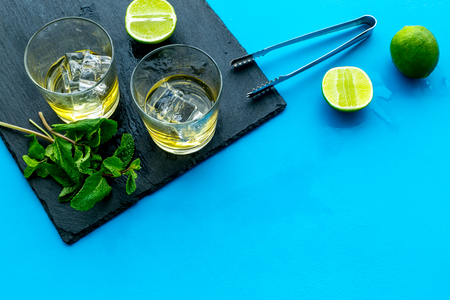 Composition with whiskey. Iced whiskey near mint, lime, bar tongs on black board on blue background top view space for text Stock Photo