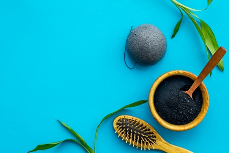 Hair care, hair spa. Cosmetics based on bamboo charcoal powder near comb on blue background top view space for text Stock Photo - 116351787