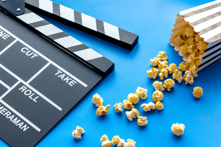 Film watching concept. Clapperboard and popcorn on blue background Banque d'images - 116351860