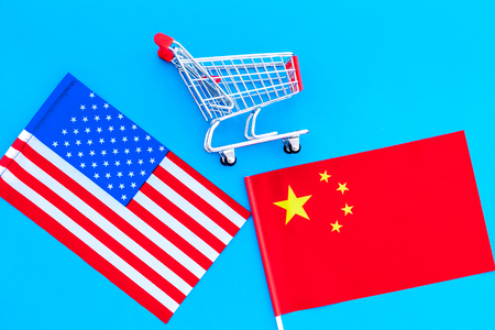 USA and China trade war. American and Chinese flags near shopping chart on blue background top view Stock Photo