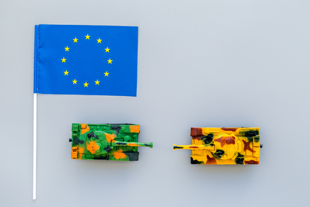 War, military threat, military power concept. European Union. Tanks toy near European flag on grey background top view copy space
