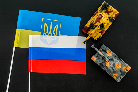 War, confrontation concept. Russia, Ukraine. Tanks toy near Russian and Ukrainian flag on black background top view Stock Photo - 116351914