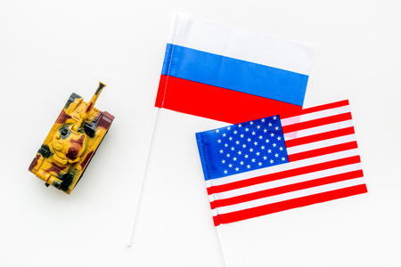 War, confrontation concept. Russia, USA. Tanks toy near Russian and American flag on white background top view