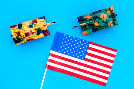 War, military threat, military power concept. USA. Tanks toy near American flag on blue background top view
