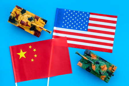 War, confrontation concept. China, USA. Tanks toy near Chinese and American flag on blue background top view