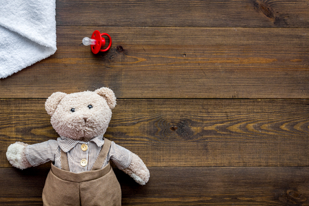 Baby care. Newborn baby concept. Teddy bear toy near pacifier on dark wooden background top view copy space