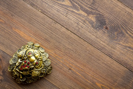 Buddhist symbol. Oriental three legged toad with gold coins on dark wooden background top view copy space Stock Photo - 116351960