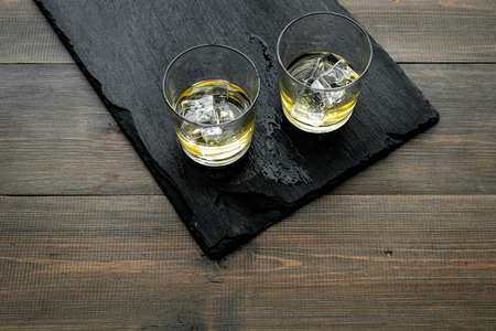 In the bar. Whiskey with ice on black desk on wooden background top view space for text