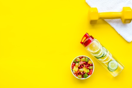Healthy lifestyle, healthy habits. Detox water, fruit salad, sport equipment dumbbells on yellow background top view copy space