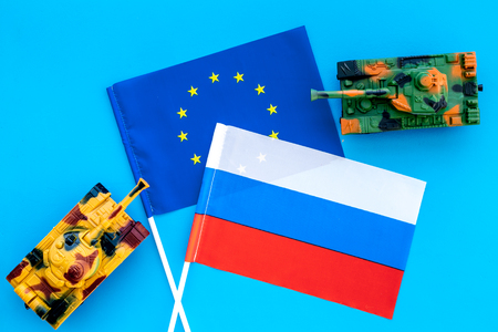 War, confrontation concept. European Union, Russia. Tanks toy near European and Russian flag on blue background top view