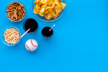 Snacks for TV watching. Chips, nuts, soda, rusks on blue background top view space for text Stock Photo