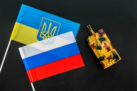 War, confrontation concept. Russia, Ukraine. Tanks toy near Russian and Ukrainian flag on black background top view Stock Photo