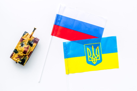 War, confrontation concept. Russia, Ukraine. Tanks toy near Russian and Ukrainian flag on white background top view