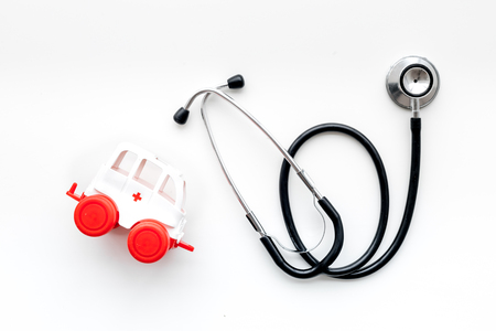 Ambulance service concept. Ambulance vehicle toy near stethoscope on white background top view.