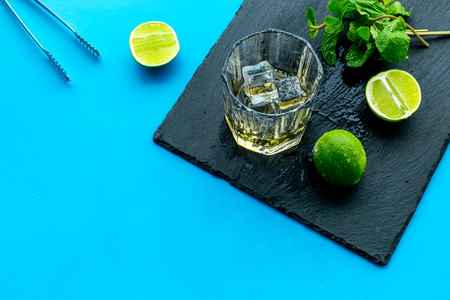 Composition with whiskey. Iced whiskey near mint, lime, bar tongs on black board on blue background top view.
