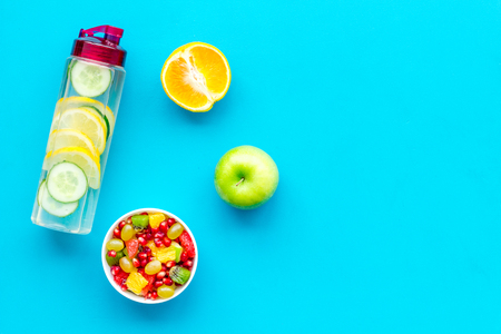 Diet rich in fruits. Slimming diet. Fruit salad near fruit lemon and cucumber water on blue background top view.