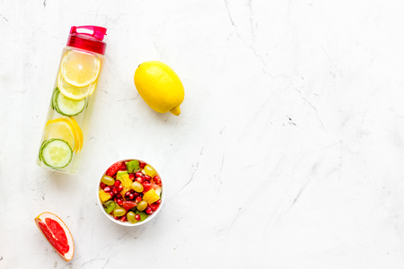 Diet rich in fruits. Slimming diet. Fruit salad near fruit lemon and cucumber water on white stone background top view.