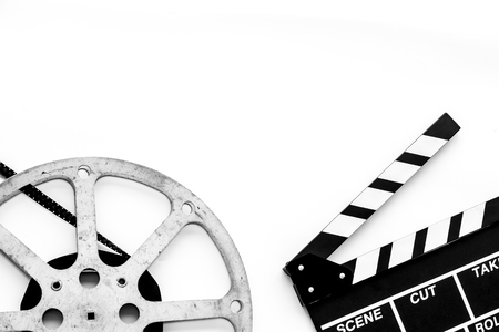 Filming concept. Clapperboard and film stock on white background top view.