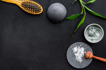 Hair care, hair spa. Cosmetics based on bamboo charcoal powder near comb on black background top view. Stock Photo