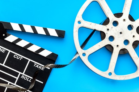Filming concept. Clapperboard and film stock on blue background top view copy space Banque d'images - 116357073