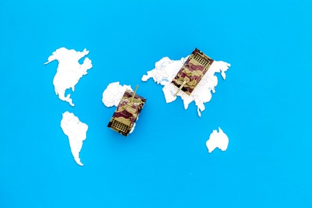 Military action, military threat concept. Tanks toy on world map on blue background top view.