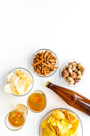 Snacks and beer. Chips, nuts, rusks near beer on white background top view space for text Stock Photo