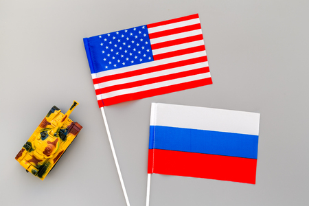 War, confrontation concept. Russia, USA. Tanks toy near Russian and American flag on grey background top view